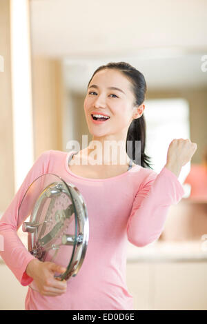 Happy young woman holding weight scale - Stock Photo
