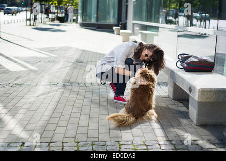 Young woman stroking a stray dog in street - Stock Photo