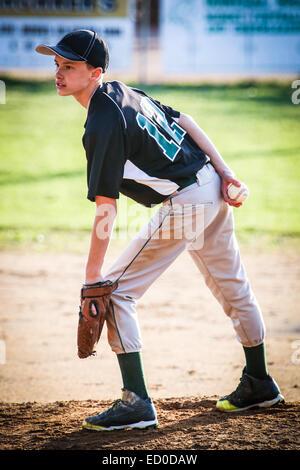 Boy standing on pitchers mound playing baseball - Stock Photo