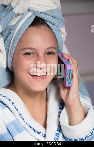 Girl sitting in her dressing gown talking on her mobile phone - Stock Photo