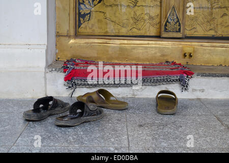 Shoes outside the door entrance of a Buddhist Wat Temple in Bangkok, Thailand. - Stock Photo
