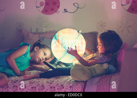 Two girls (2-3, 6-7) looking at illuminated lamp in shape of globe - Stock Photo