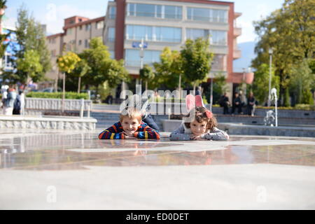Little boy (6-7) and girl (4-5) playing outside - Stock Photo