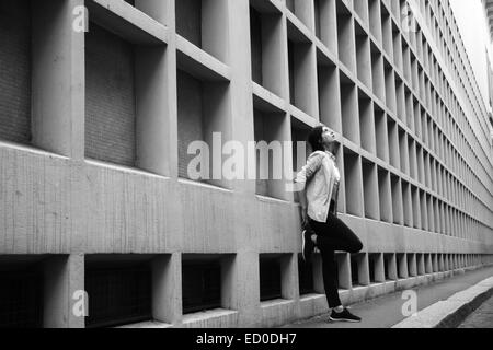 Italy, Milan, Woman leaning against wall - Stock Photo