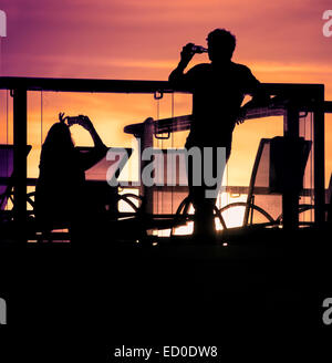 England, Southampton, Silhouettes of couple relaxing on balcony at sunset - Stock Photo