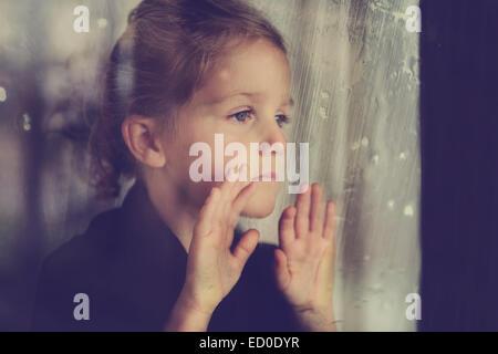 Girl (4-5) looking through wet window - Stock Photo