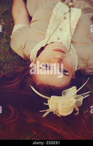 Portrait of red hair woman laying on grass - Stock Photo