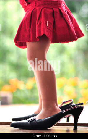 Girl wearing her mother's high heel shoes - Stock Photo