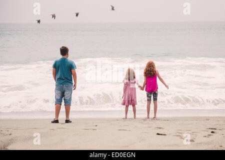 USA, California, Los Angeles, Children (6-7, 8-9, 12-13) watching waves breaking on beach - Stock Photo