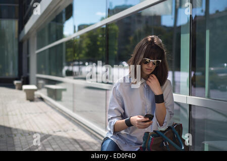 Woman sitting in street looking at mobile phone, Sofia, Bulgaria - Stock Photo