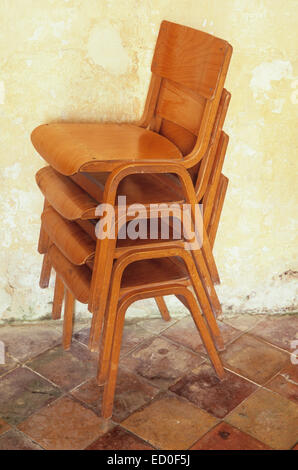 Four stacking chairs made from bent wood and plywood stacked on ochre tile floor in front of rough cream wall - Stock Photo