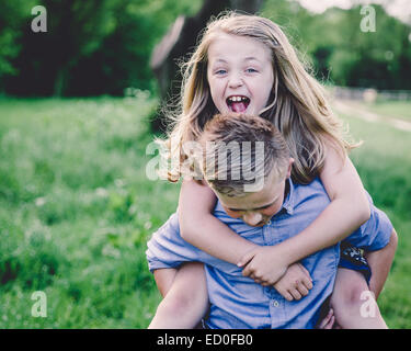 Siblings (8-9, 10-11) enjoying themselves in countryside - Stock Photo
