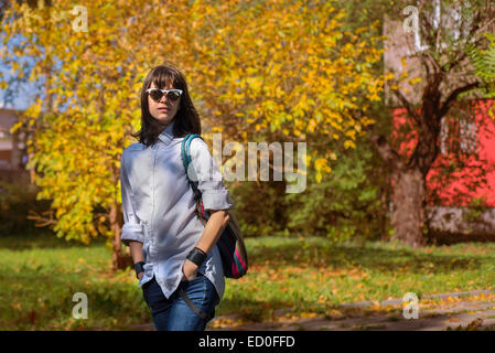 Portrait of young woman in autumn scenery - Stock Photo