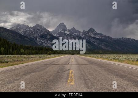 Straight road to mountains near Jackson Hole, Grand Teton National Park, Wyoming, USA - Stock Photo