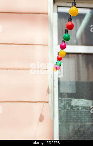 Multicolored fairy lights hanging on building - Stock Photo