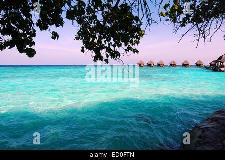 Maldives, Turquoise water and beach huts on horizon - Stock Photo