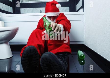 drunken santa claus sleeping at bathroom with beer bottle in hand - Stock Photo