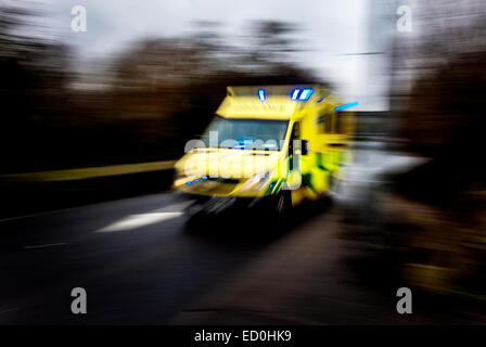 Fast moving ambulance responding to an emergency image showing speed blur. - Stock Photo