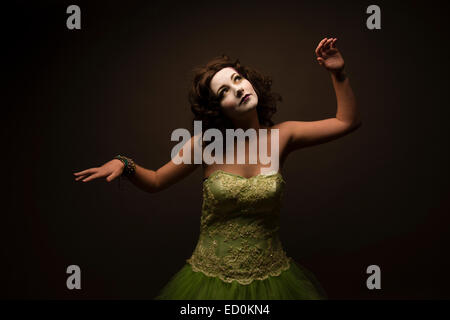 Fantasy makeover photography: A young woman girl model made up to look like a porcelain white-faced painted puppet - Stock Photo
