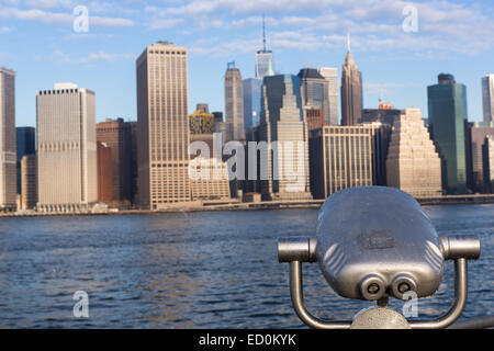 Lower Manhattan skyline viewed from the Brooklyn Bridge park across the East River with a sightseeing binocular - Stock Photo