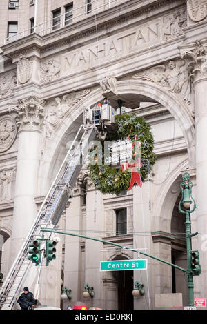 FDNY Ladder One assists municipal workers in the installation of a giant Christmas wreath on the New York Municipal - Stock Photo