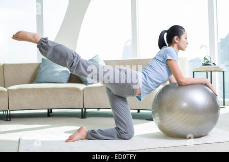 Young woman practicing yoga with fitness ball - Stock Photo