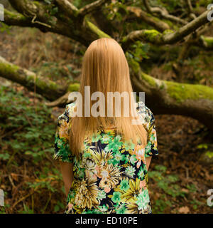 Shyness: An enigmatic image of a  young woman girl with long blonde hair hiding obscuring  covering her entire face - Stock Photo