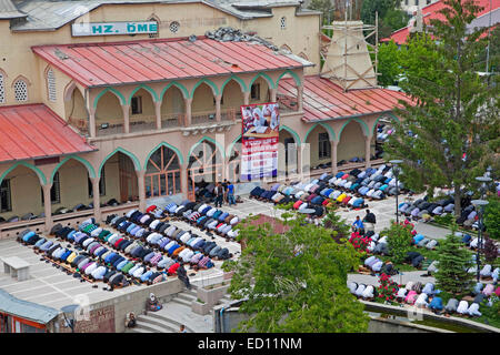Turkish and Kurdish Muslim men in prostration praying outdoors in front of Islamic mosque for Friday prayers in - Stock Photo