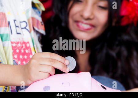 2 children Piggy Bank saving money - Stock Photo