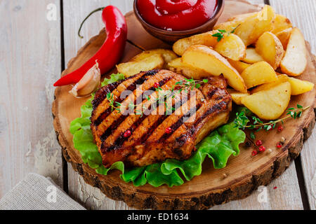 Grilled steak on the bone with potatoes - Stock Photo