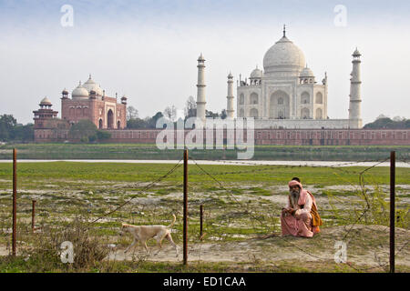 Sadhu (holy man) in front of Taj Mahal and jawab across the Yamuna River, Agra, India - Stock Photo