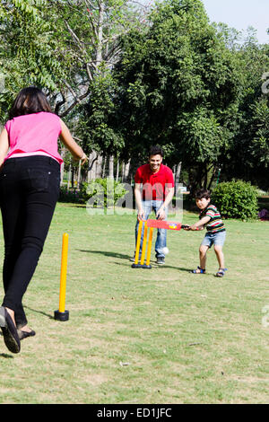 indian Parents with child  park Playing Cricket - Stock Photo