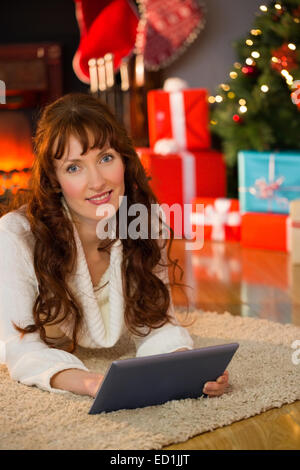 Redhead woman lying on floor using tablet at christmas - Stock Photo