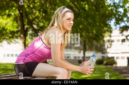 Fit blonde taking a break in the park - Stock Photo