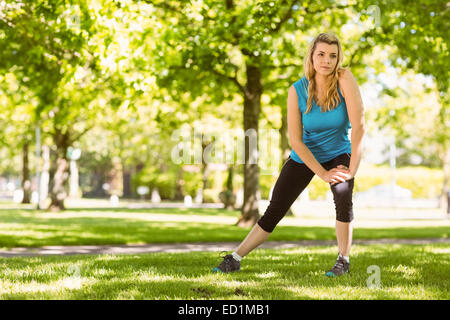 Fit blonde stretching on the grass - Stock Photo