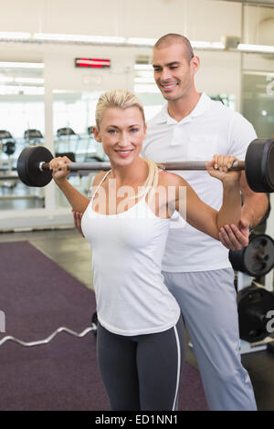 Male trainer helping woman with lifting barbell in gym - Stock Photo