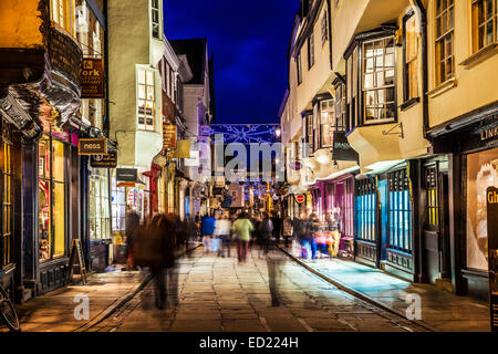 Christmas shoppers hurrying along the historic street of Stonegate in York at twilight. - Stock Photo