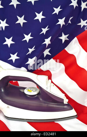 Electric iron smoothing the folds of the American flag - Stock Photo