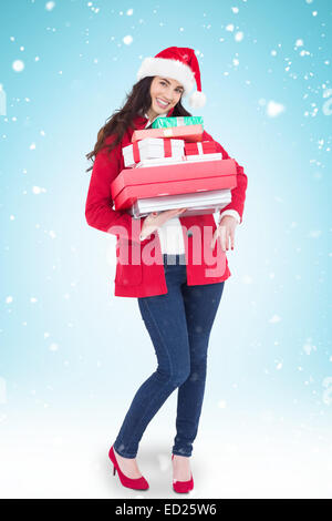 Composite image of festive brunette in santa hat and red coat holding pile of gifts - Stock Photo