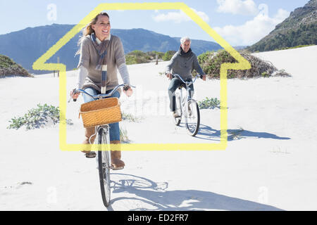 Composite image of carefree couple going on a bike ride on the beach - Stock Photo