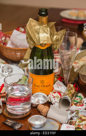 Debris in the aftermath of a festive season party with an empty Veuve Clicquot champagne bottle and other rubbish - Stock Photo