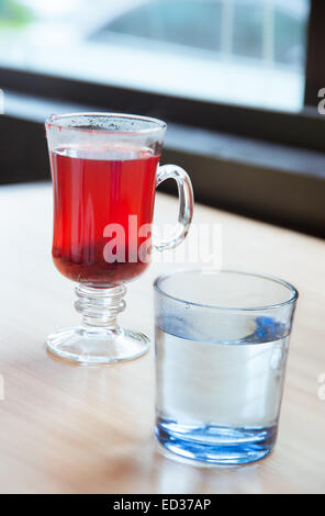 Red cranberry fruit drinks and vodka in glass on table - Stock Photo