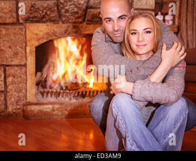 Portrait of gentle couple sitting near fireplace at home, romantic celebration of Christmas holidays, love and togetherness - Stock Photo