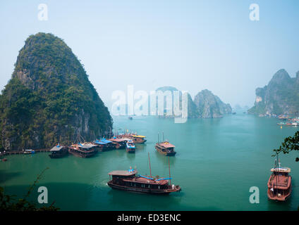 A view of the spectacular limestone karst formations rising above boats moored in Halong Bay, Vietnam. - Stock Photo