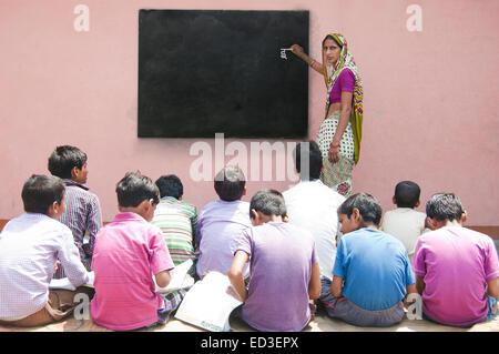 indian rural Teacher woman Teaching Children - Stock Photo