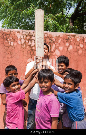 indian rural group children boys Playing cricket - Stock Photo