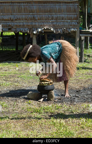 Melanesia, Papua New Guinea, Dobu Island. Village woman in grass skirt cooking with typical pottery crock over open - Stock Photo