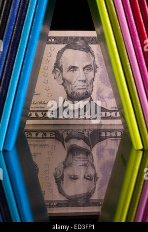 Twelve different colors diaries and US dollar banknote on a glass desk - Stock Photo
