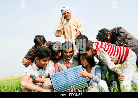 indian rural  Farmer family with Business Man laptop working - Stock Photo