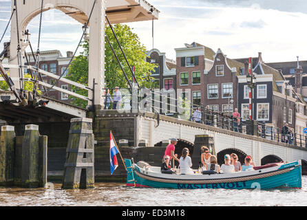 Amsterdam Amstel River with Skinny Bridge, Magere Brug with electric rental boat with girls young women partying, - Stock Photo